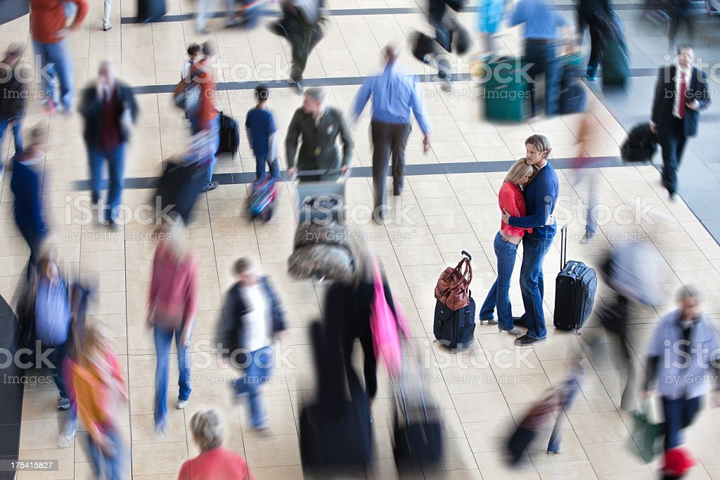 Couple embraced in crowded airport royalty-free stock photo