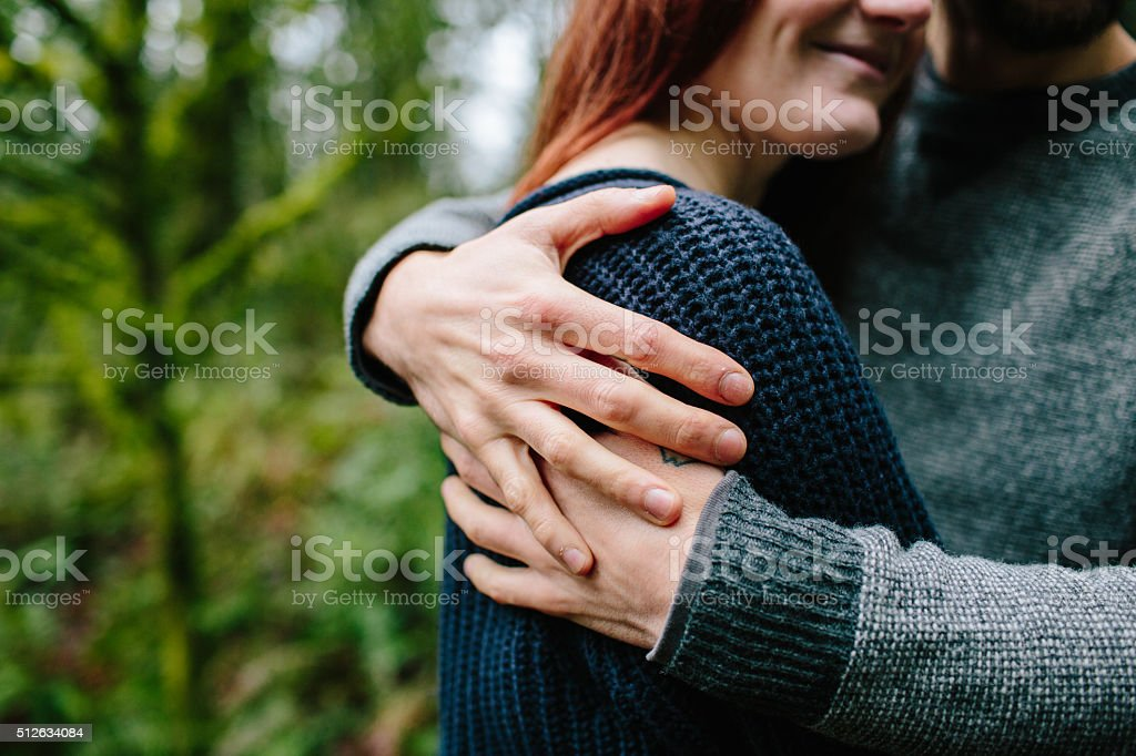 Couple embraces in the woods stock photo