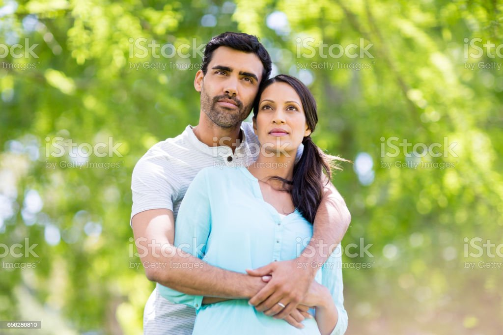 Couple embracing each other in park stock photo