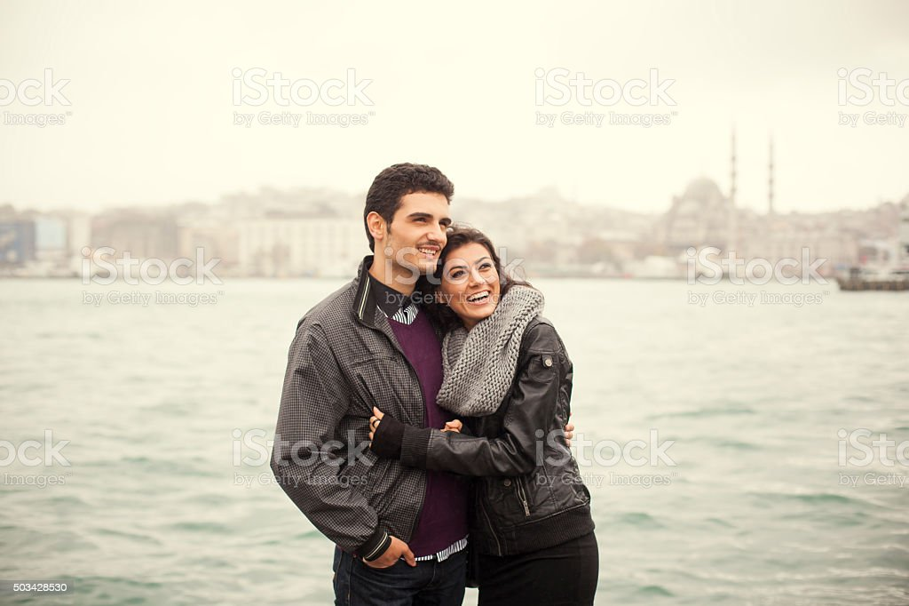 Couple Embracing Each Other Near The Sea with City View stock photo