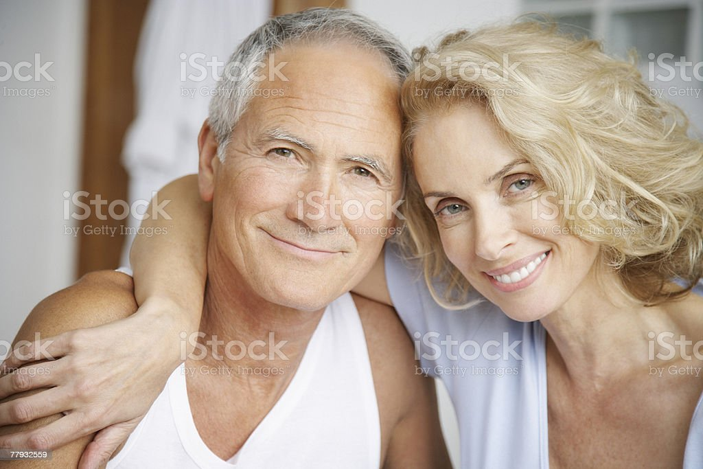 Couple embracing in bedroom stock photo