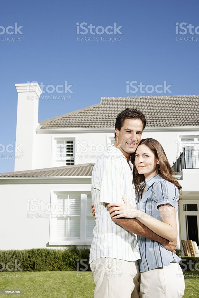 A couple embracing in front of a large home royalty-free stock photo