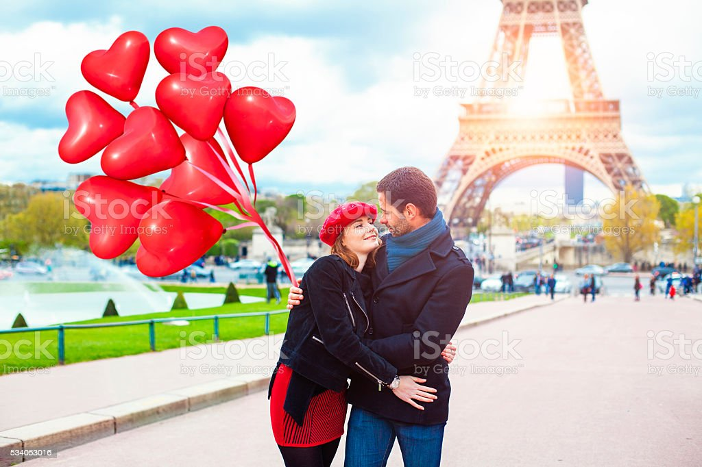 Couple embracing in front of the Effiel Tower Paris stock photo