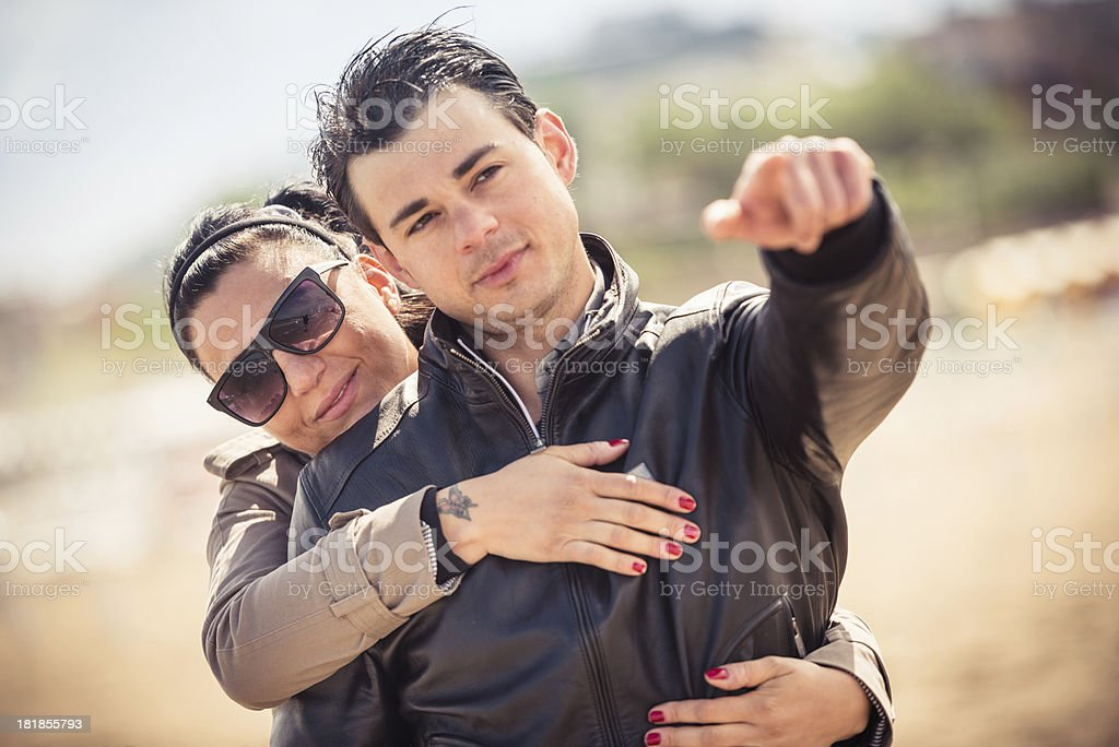 couple embracing on summer and pointing the arm royalty-free stock photo