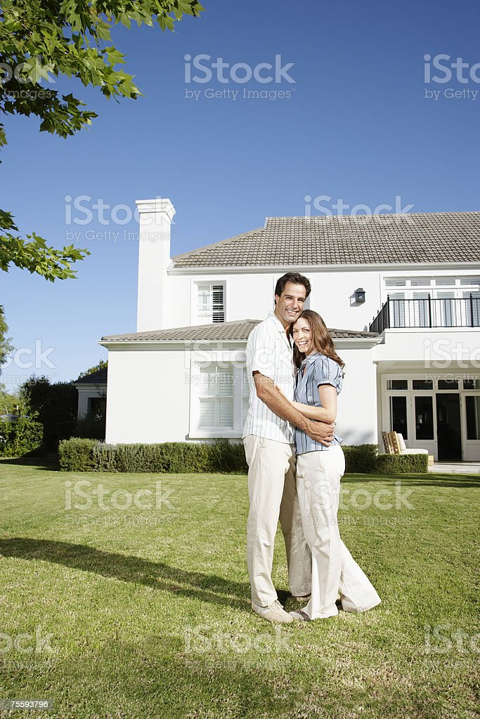 A couple embracing on the front lawn of a large home royalty-free stock photo