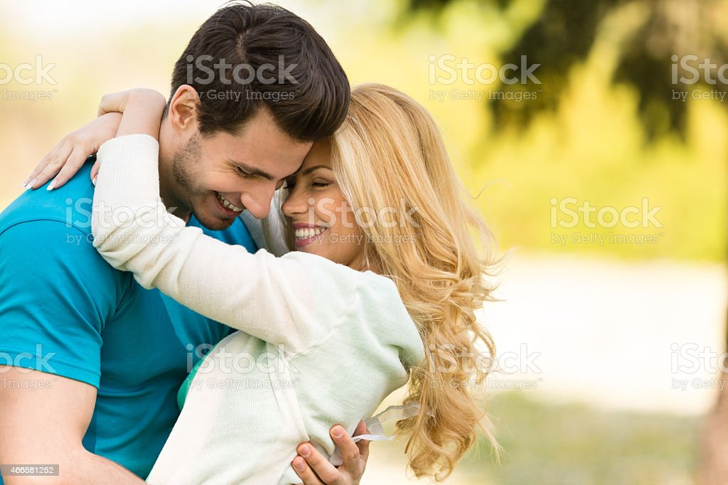 Couple embracing outdoors in spring park stock photo