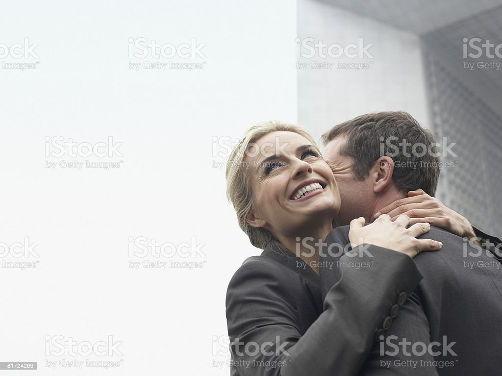 Couple embracing outdoors near building smiling royalty-free stock photo
