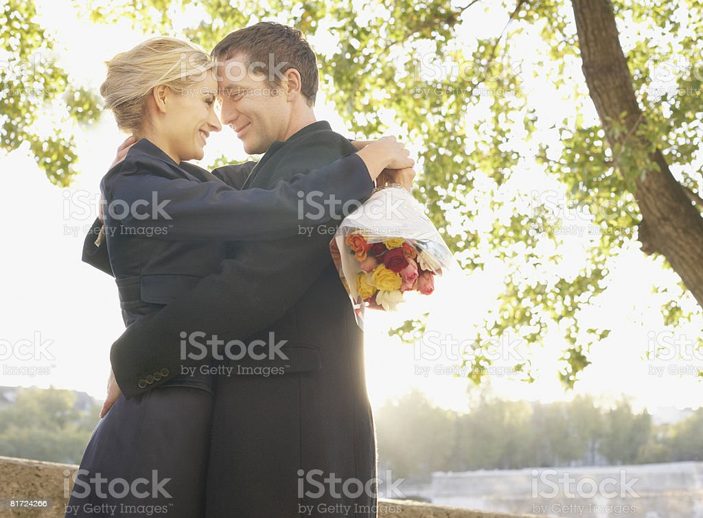 Couple embracing outdoors with flowers smiling stock photo