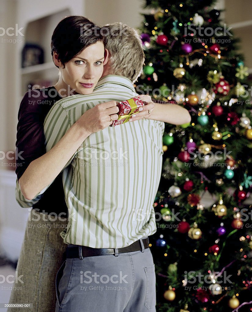 Couple embracing, woman holding christmas present, portrait royalty-free stock photo
