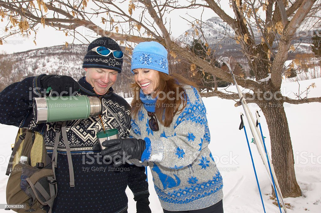 Couple Enjoying a Break While Out Skiing stock photo