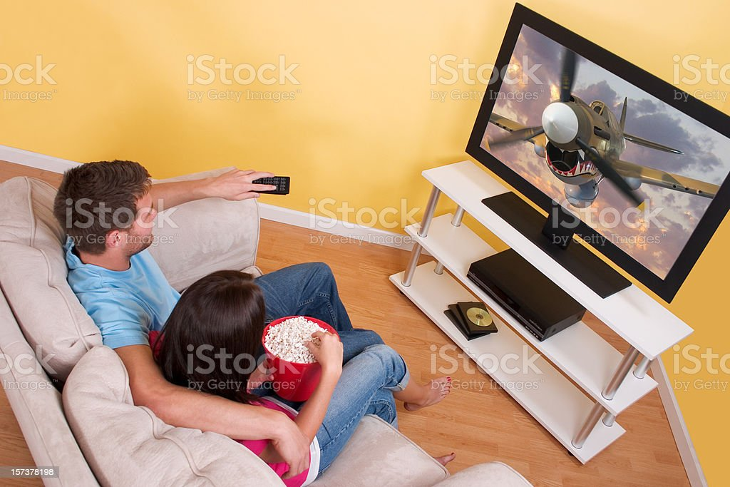 A couple enjoying a cartoon on TV with popcorn royalty-free stock photo