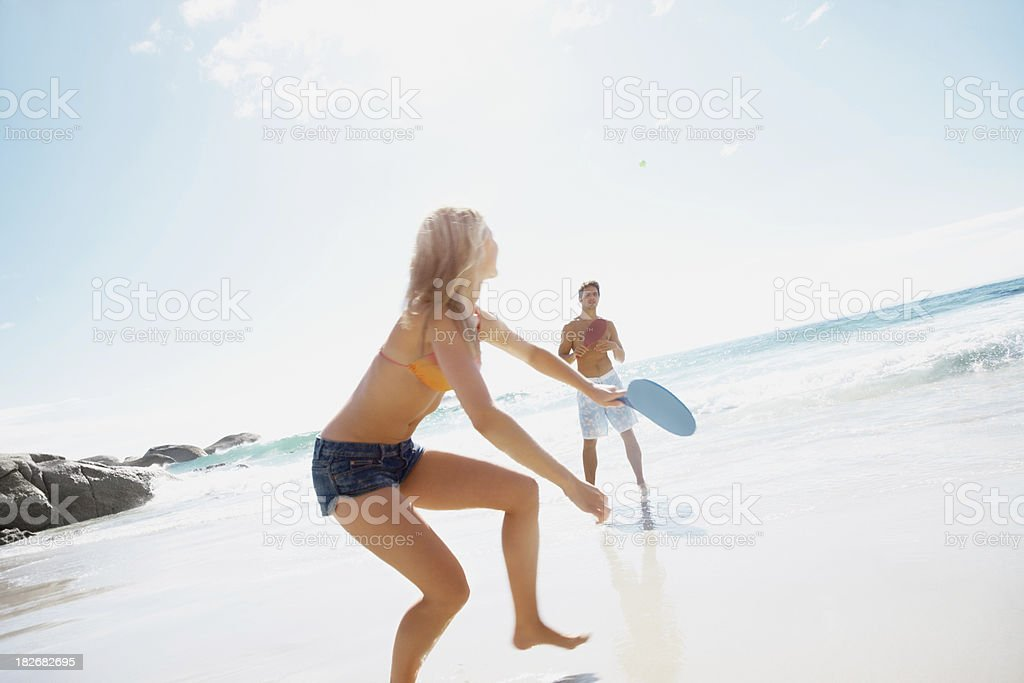 Couple enjoying a racket game at the beach royalty-free stock photo