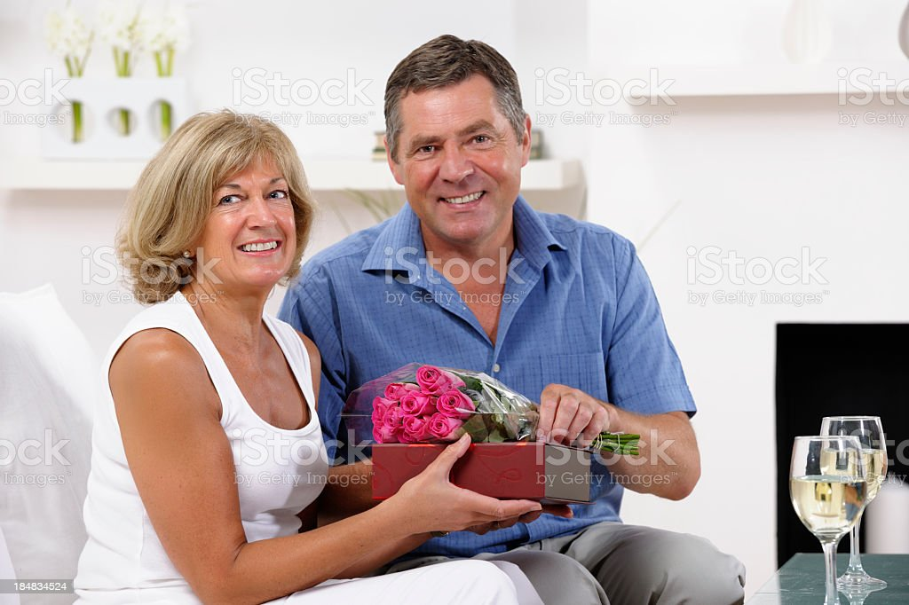 Couple Enjoying A Romantic Moment- Exchanging Flowers And Gifts royalty-free stock photo