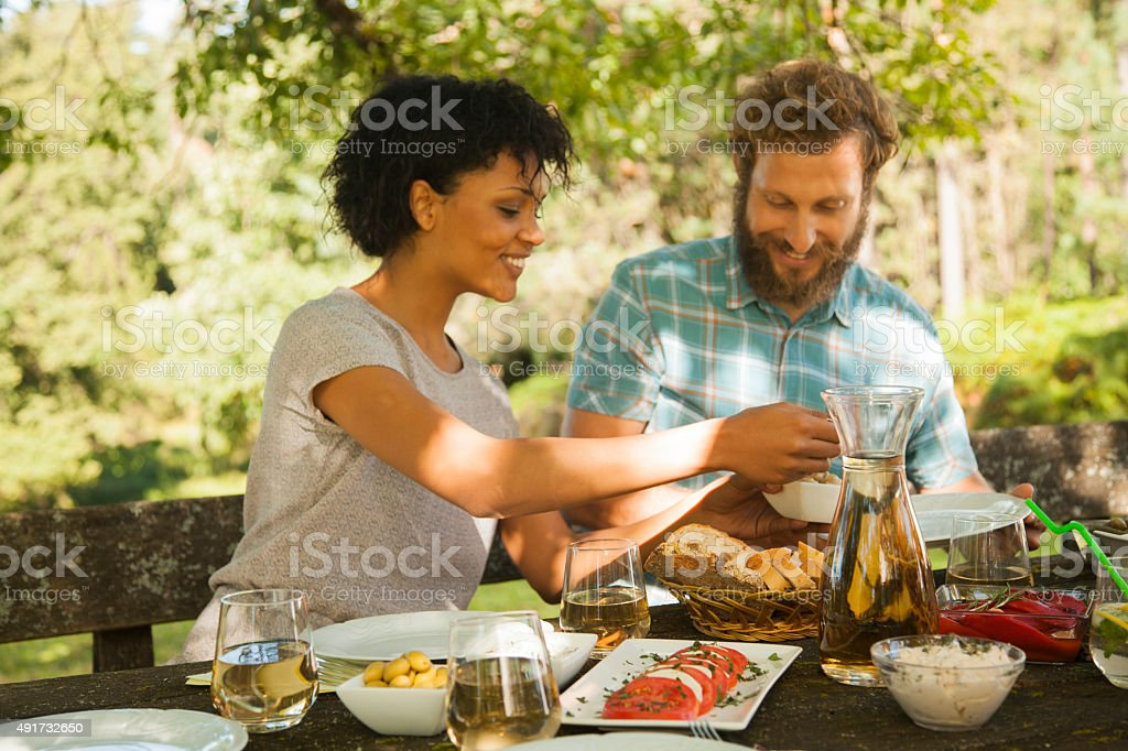 Couple enjoying barbecue at outdoors stock photo