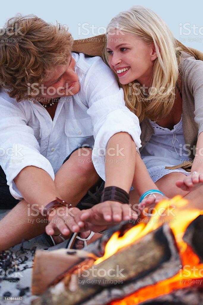 Couple enjoying bonfire on the beach royalty-free stock photo