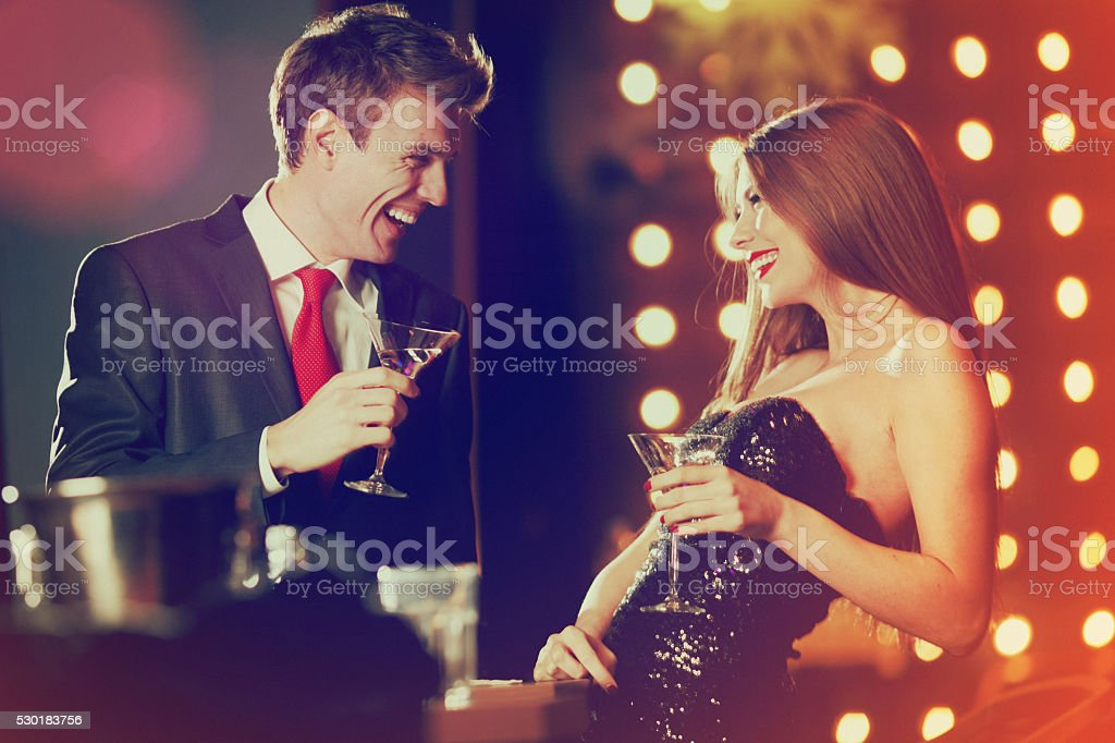 couple enjoying coctails in luxury bar stock photo