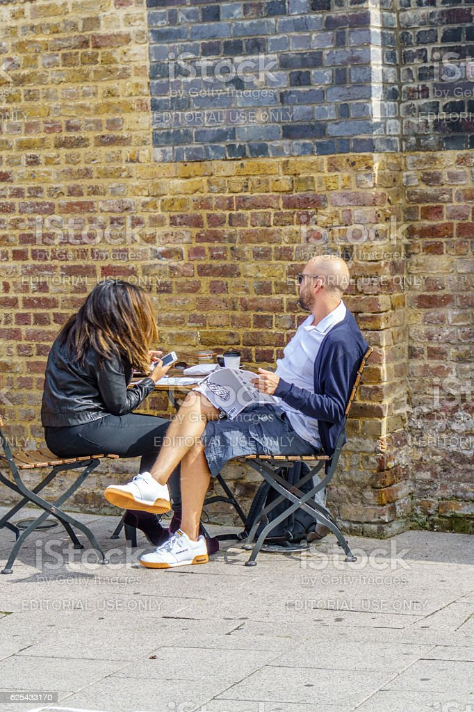Couple enjoying coffee outside Hoxton Station on London Overground stock photo