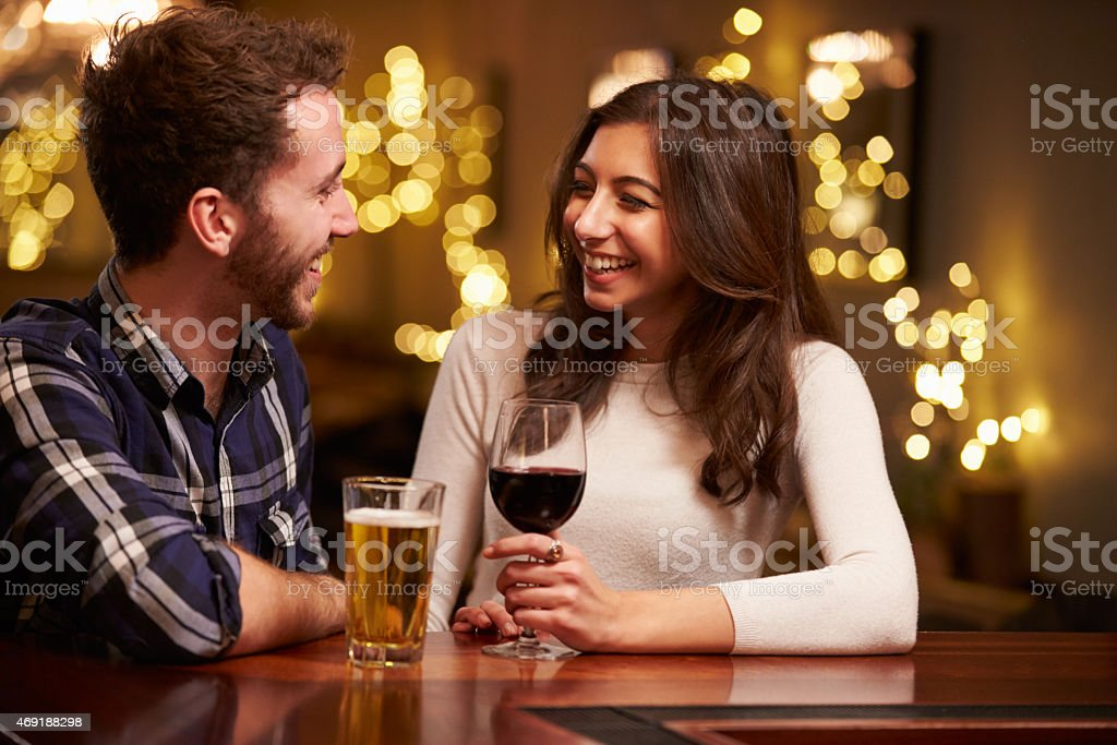 Couple Enjoying Evening Drinks In Bar stock photo