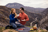 Couple enjoying in cup of coffe and tea on picnic.