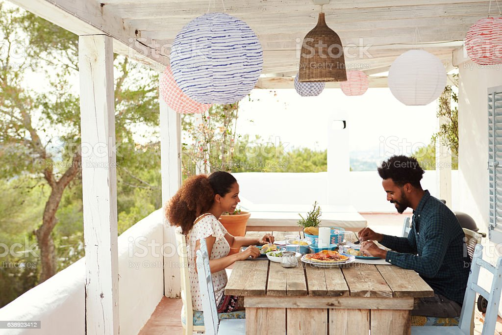 Couple Enjoying Outdoor Meal On Terrace Together stock photo