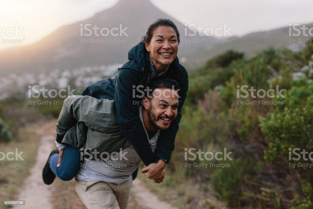 Couple enjoying piggyback ride in countryside stock photo