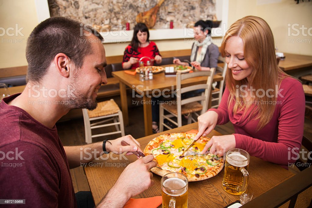 Couple enjoying pizza in a full pizzeria stock photo
