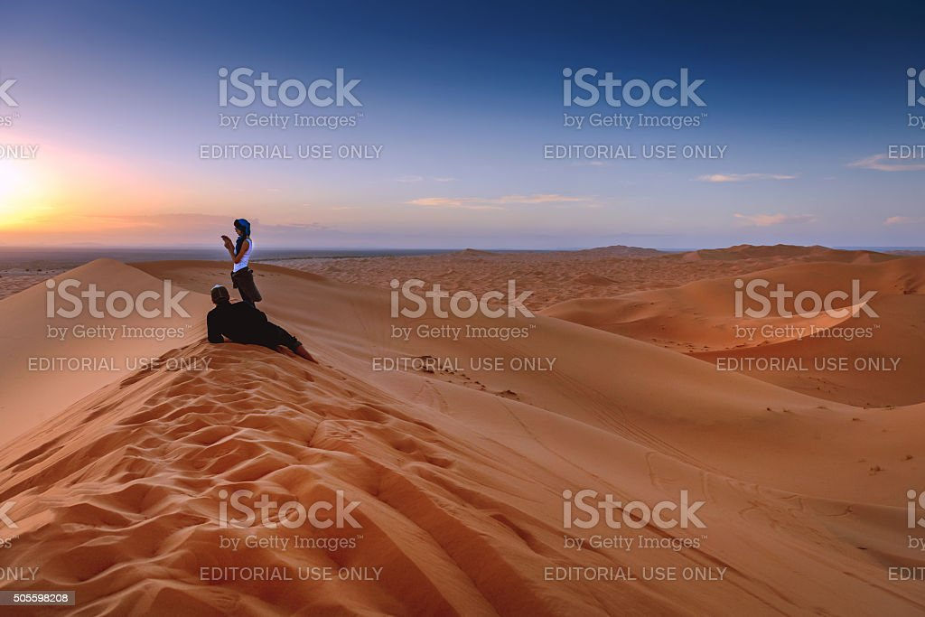 Couple enjoying sunset Erg Chebbi Sand Dunes, Morocco,  Northern Africa stock photo