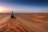 Couple enjoying sunset Erg Chebbi Sand Dunes, Morocco,  Northern Africa