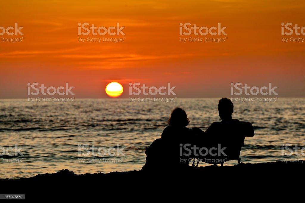 Couple Enjoying Sunset on the Beach of Hawaii stock photo
