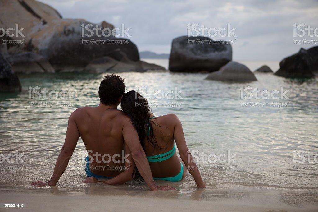 couple enjoying sunset on tropical beach in the Caribbean stock photo