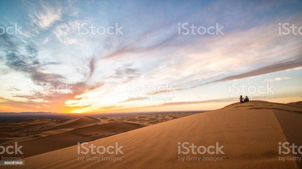 A couple enjoying the sunset on the dunes of the Sahara Desert in Merzouga - Morocco stock photo