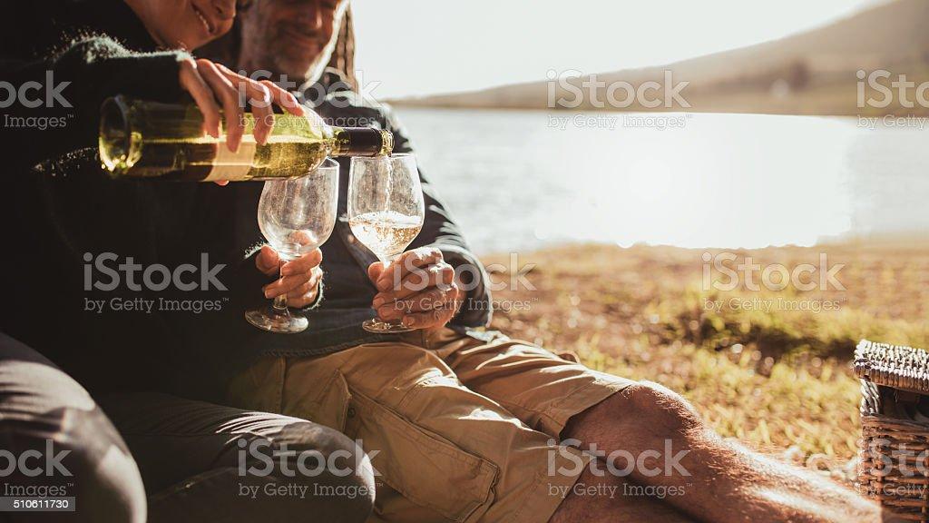 Couple enjoying wine on camping trip stock photo