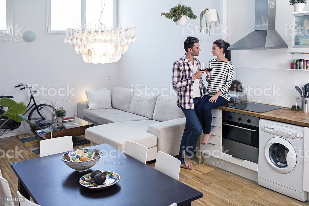 Couple enjoying with a glass of wine in their apartment royalty-free stock photo