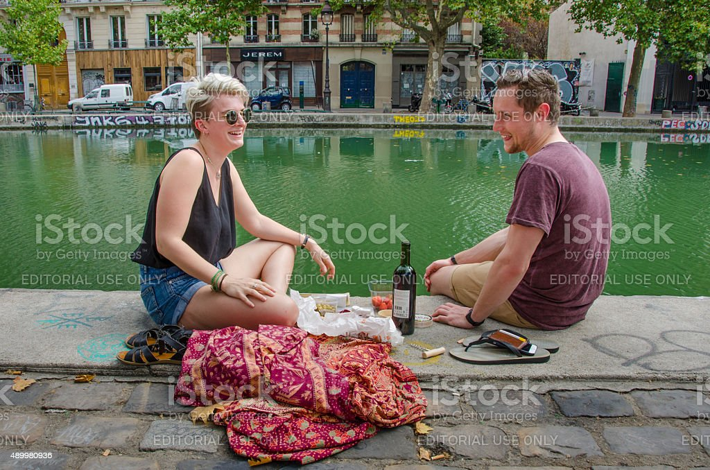 Couple enjoys lunch at Canal Saint-Martin in Paris stock photo