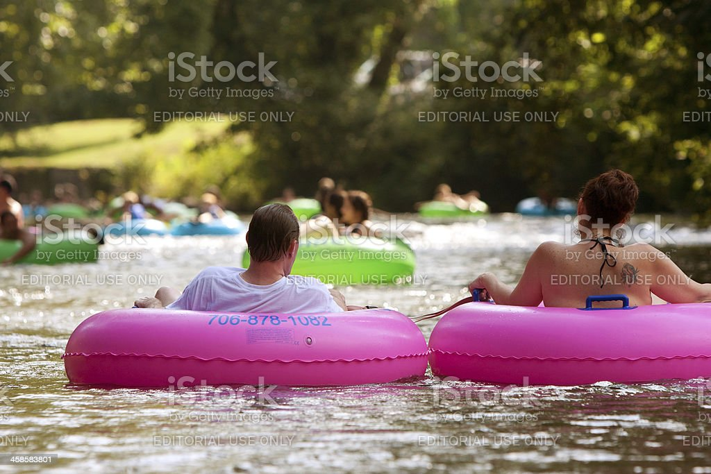 Couple Enjoys Tubing Down River In Summer Heat stock photo