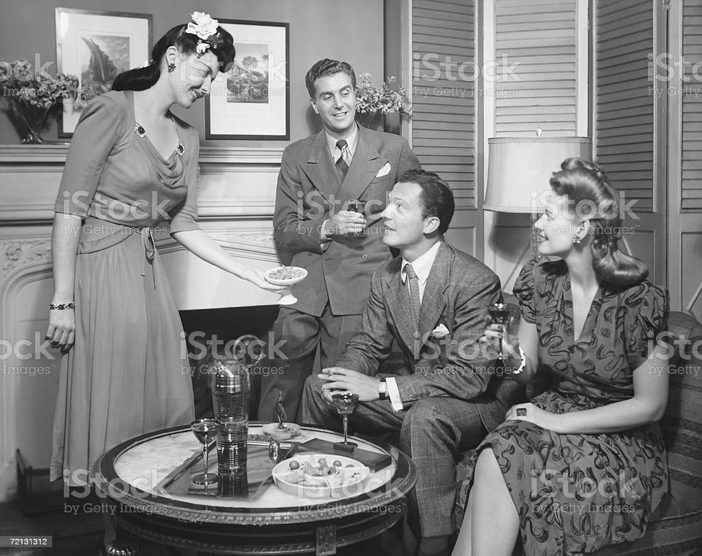 Couple entertaining friends (B&W) stock photo