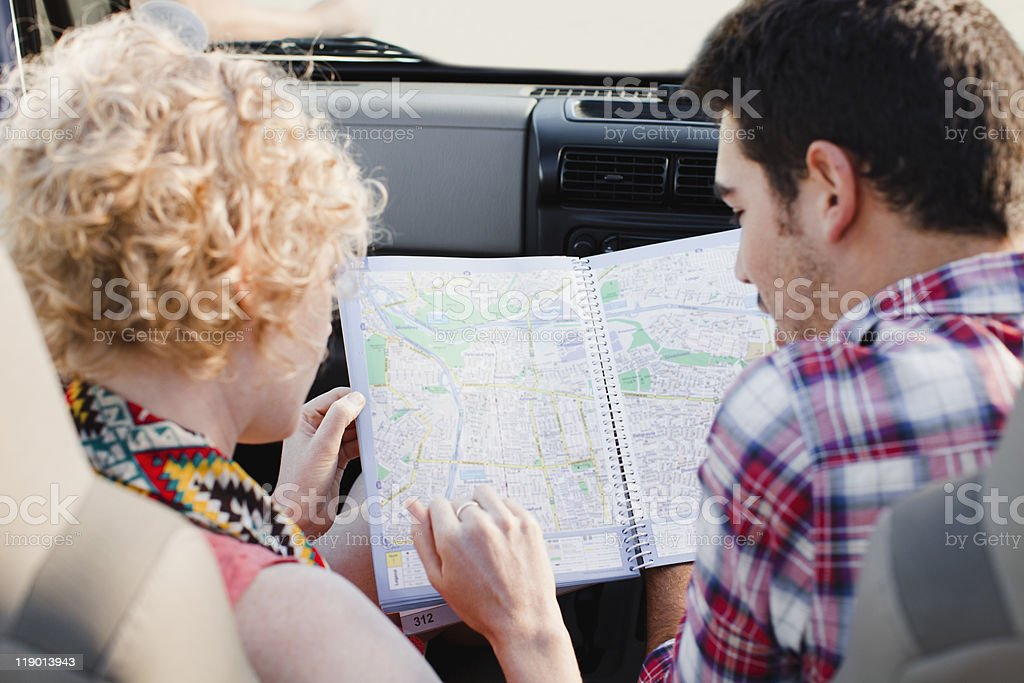 Couple examining map in jeep stock photo