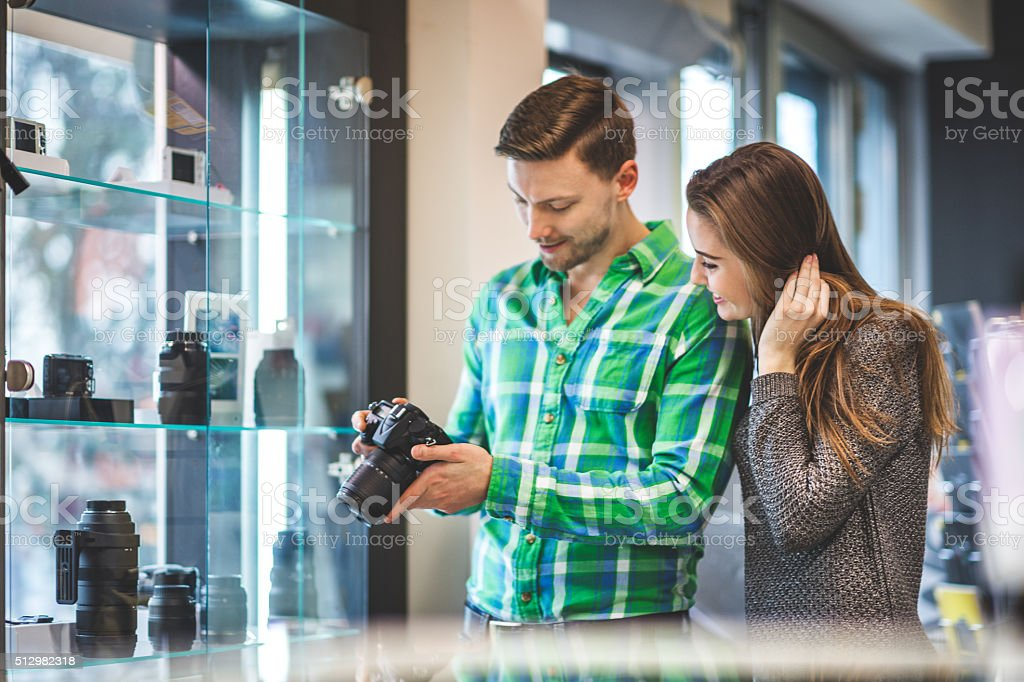 Couple examining SLR camera in the store stock photo