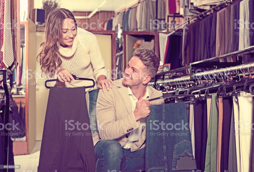 Couple examining various trousers stock photo