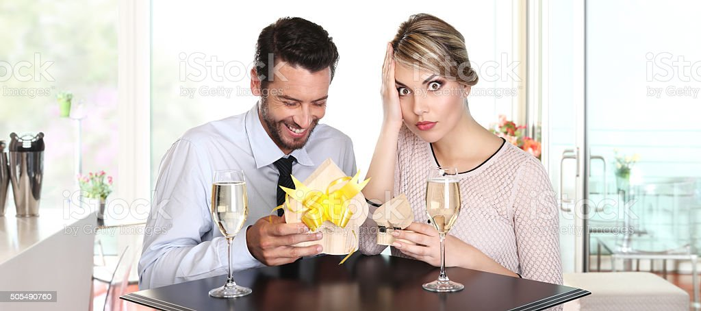 couple exchanging gifts on a date, to the surprise stock photo