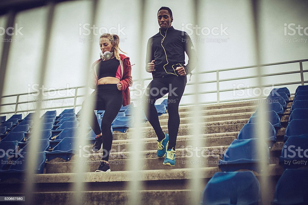 Couple exercise together on the stands at the stadium stock photo