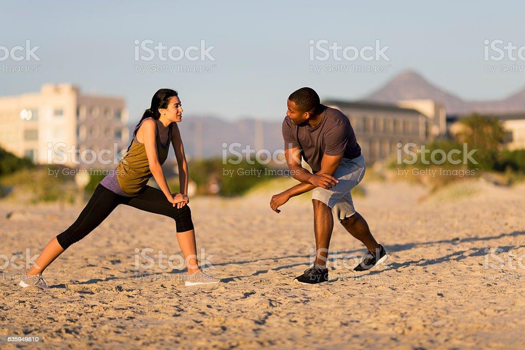 Couple exercising at beach stock photo