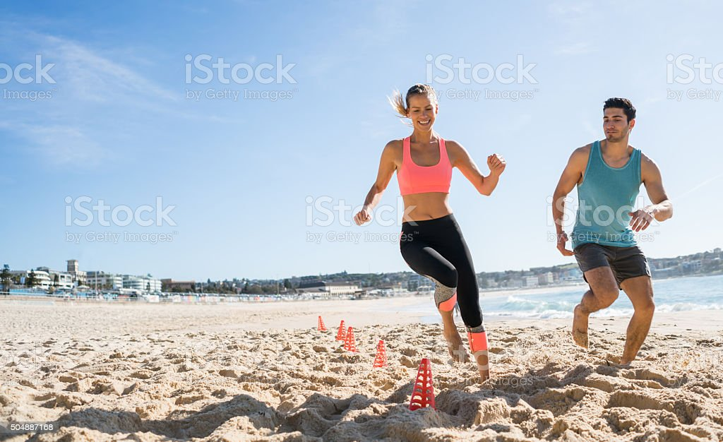Couple exercising outdoors at the beach stock photo