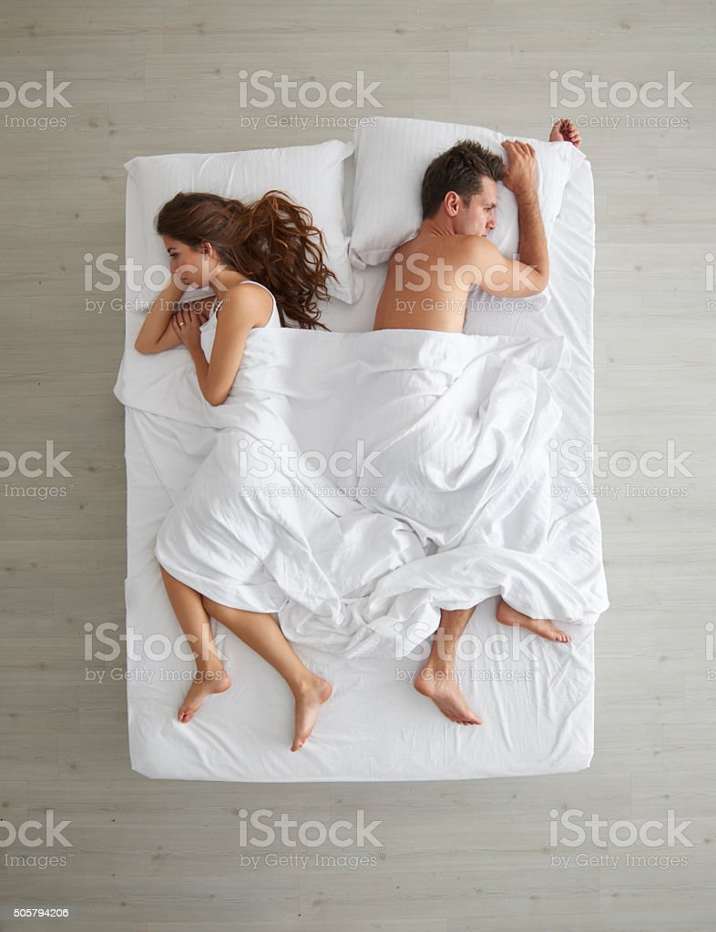 Couple facing away from each other in bed stock photo