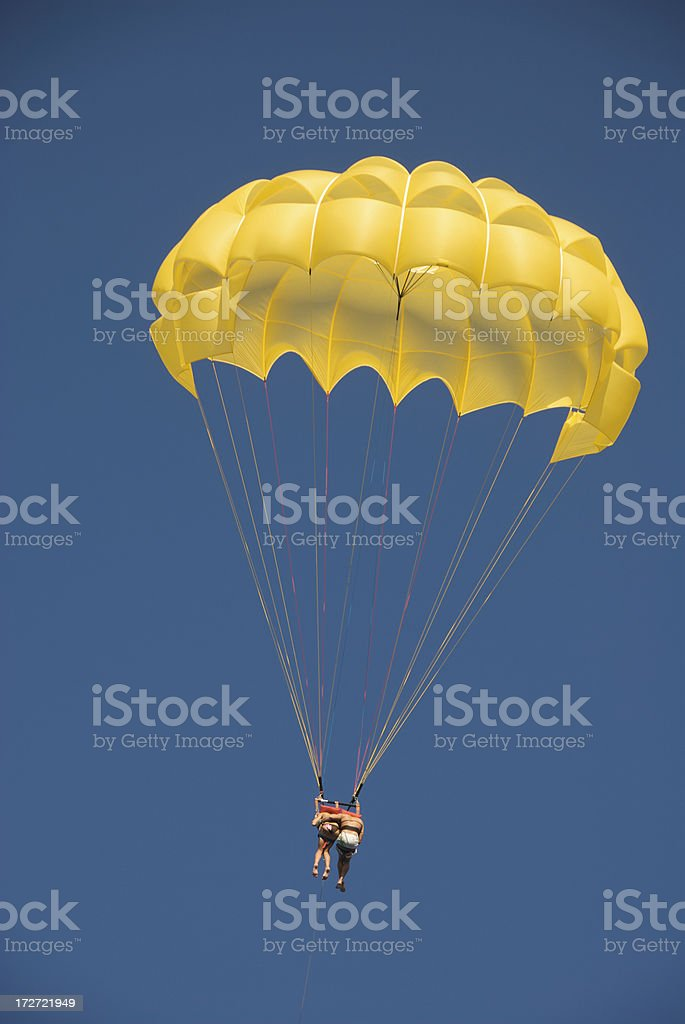 Couple Falling Together in Yellow Parachute Blue Sky stock photo