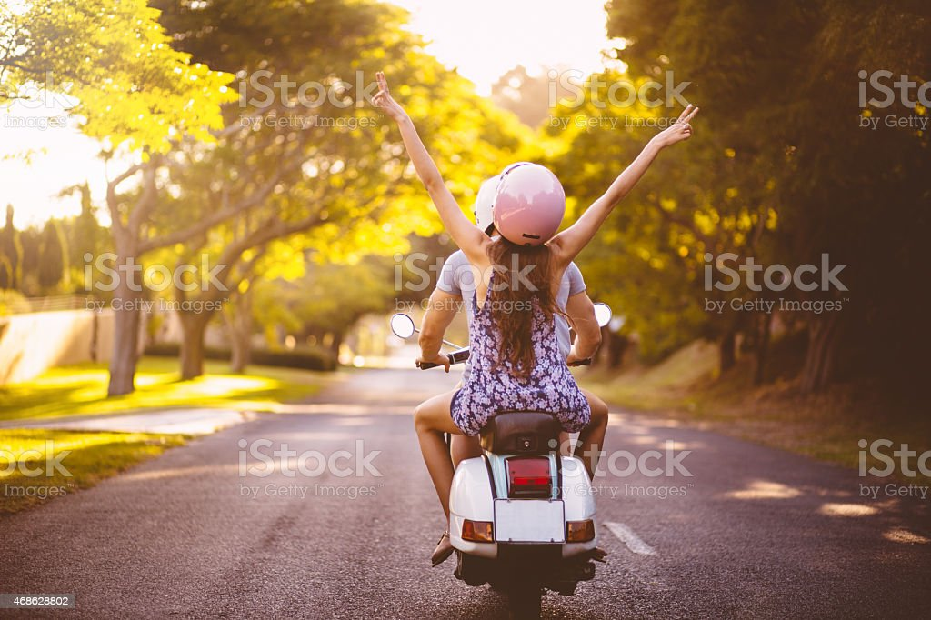Couple feeling free on their scooter while road tripping stock photo