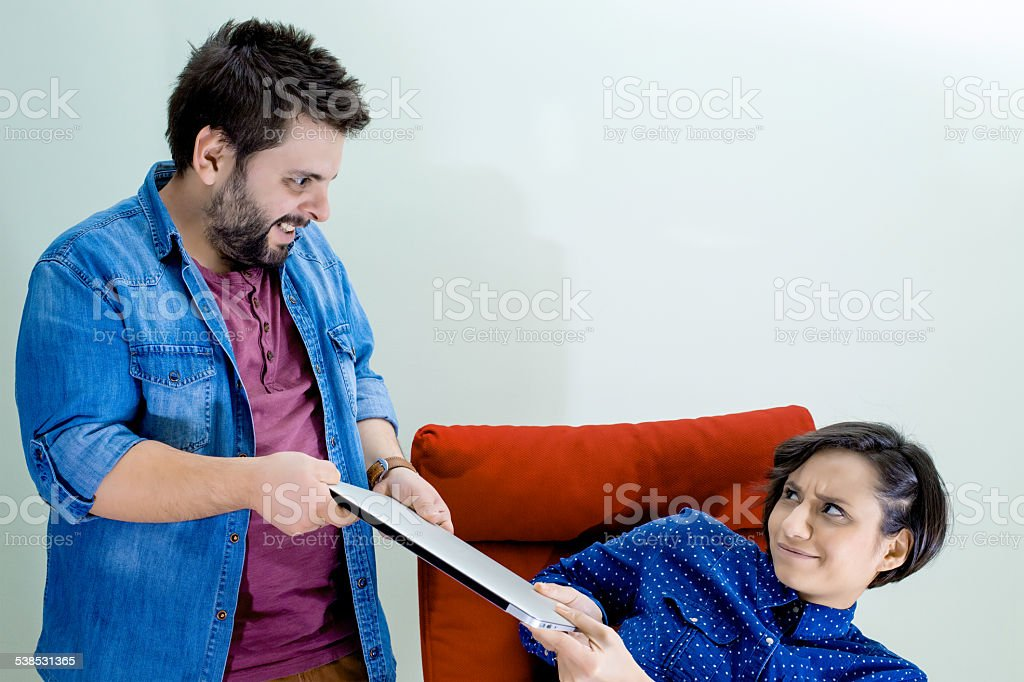 couple Fighting for the laptop stock photo
