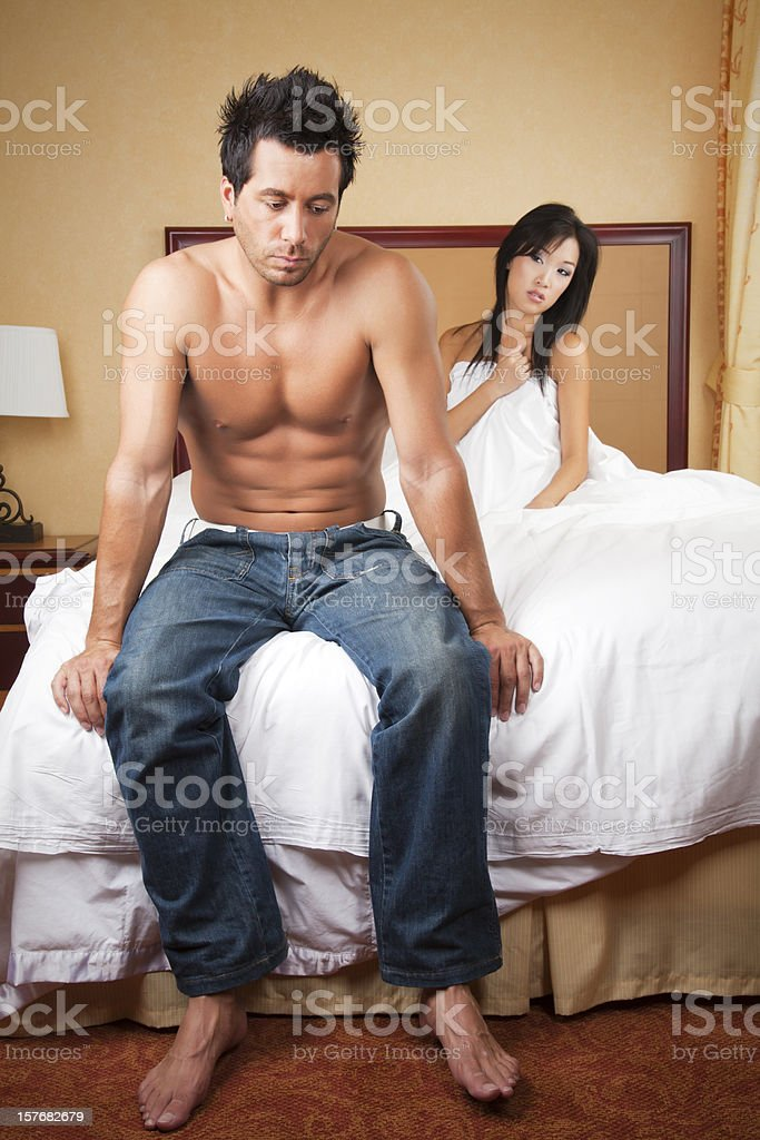 Couple fighting: Upset man sitting on edge of the bed royalty-free stock photo