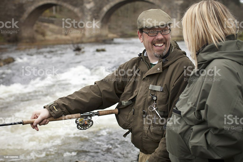 Couple fishing for salmon in river stock photo