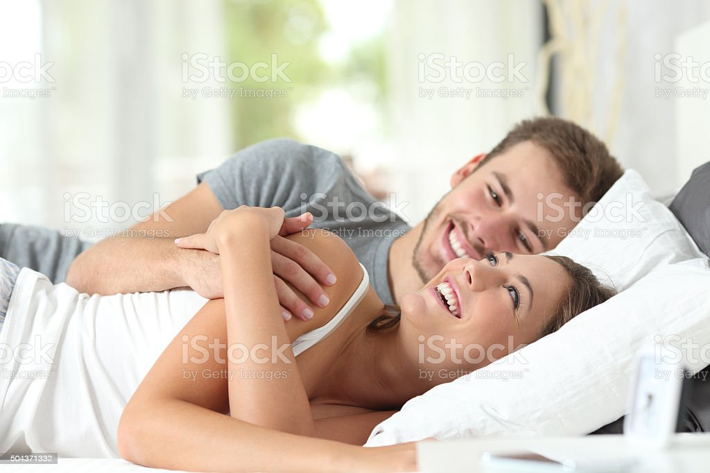 Couple flirting on a bed at home stock photo